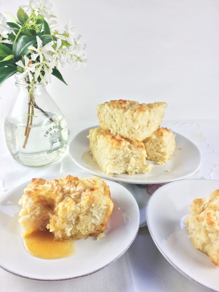 Shows buttermilk biscuit covered with honey, with more biscuits on plates around it and a vase of white flowers