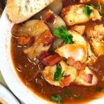 Fish stew with a slice of bread at top corner. Shows fish, egg, bacon