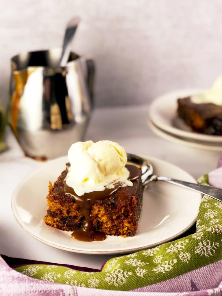Sticky Toffee Pudding Cake with cup of toffee sauce