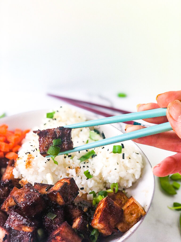Shows cube of marinated crispy tofu in chopsticks hovering over rice bowl