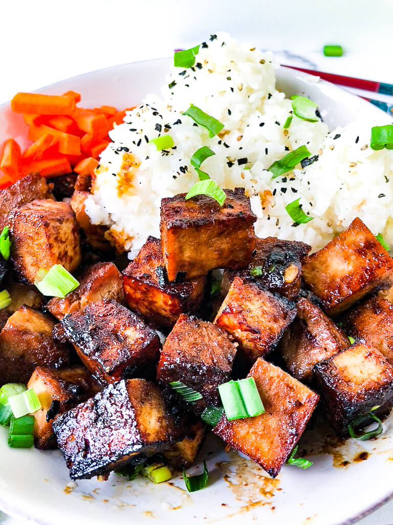 Bowl of crispy tofu and rice with furikake and scallions