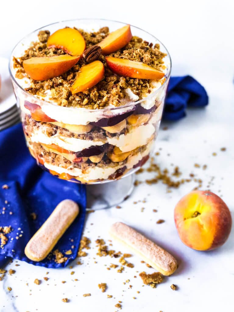 Featured Photo for Peach Crisp Trifle showing the trifle from above with scattered ingredients including lady fingers, baked crisp and fresh peaches. blue napkin drapes in white background