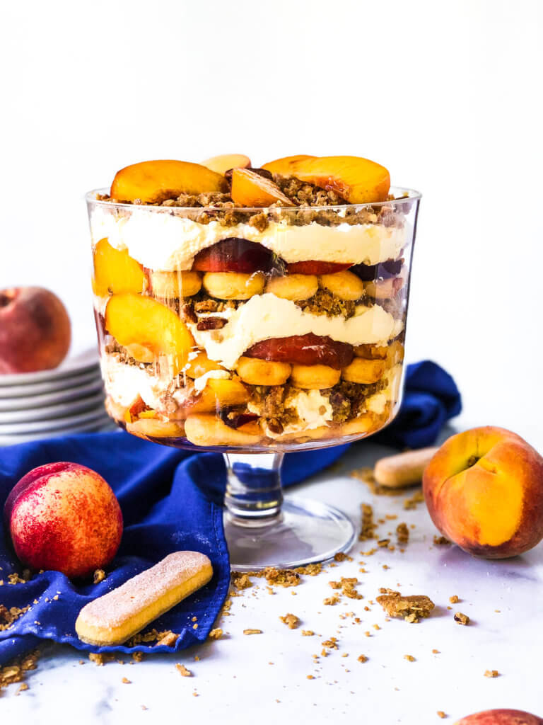 Easy Peach Crisp Trifle photo showing the trifle from above with scattered ingredients including lady fingers, baked crisp and fresh peaches. blue napkin drapes in white background