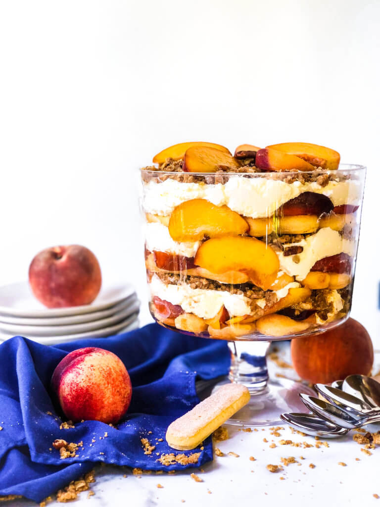 12-layered Peach Crisp Trifle showing the trifle from above with scattered ingredients including lady fingers, baked crisp and fresh peaches. blue napkin drapes in white background