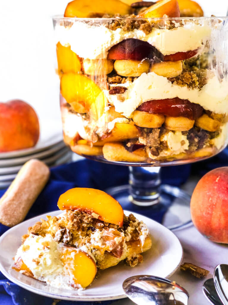 Shows slice of Easy Peach Crisp Trifle along with the 12-layered dish of trifle