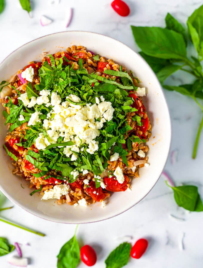 Farro Salad with roasted tomatoes, red onions and a pile of shredded mint and basil all topped with crumbled feta cheese - featured image
