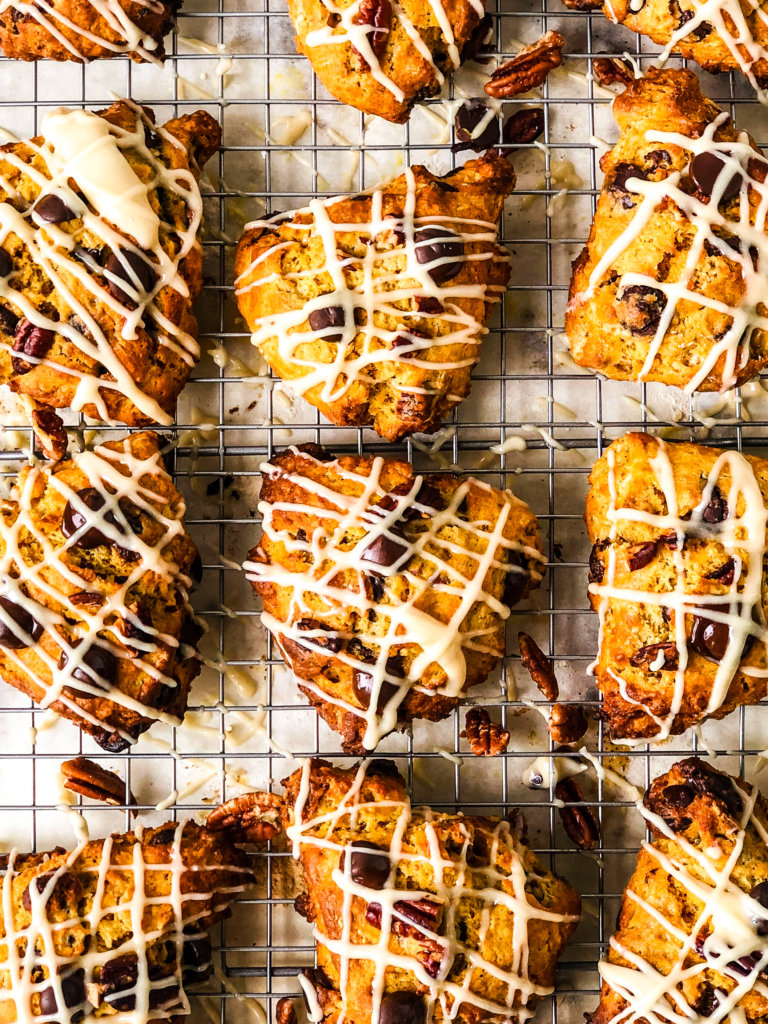 Tray with a dozen Pumpkin Chocolate Chip Scones with streaks of Brown Sugar Glaze, sitting atop baking rack over parchment paper
