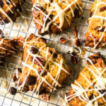 Recipe card photo, close-up of Best Pumpkin Scone Recipe with chocolate chips and pecans, drizzled with brown sugar glaze sitting atop baking rack