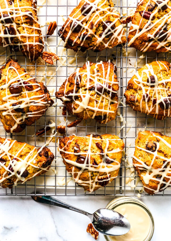 Tray of 9 pumpkin chocolate chip scones with pot of brown sugar glaze with spoon over white marble background