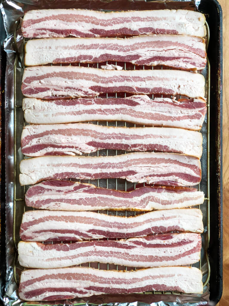 Shows sheet pan of bacon strips laid out over a grate to bake