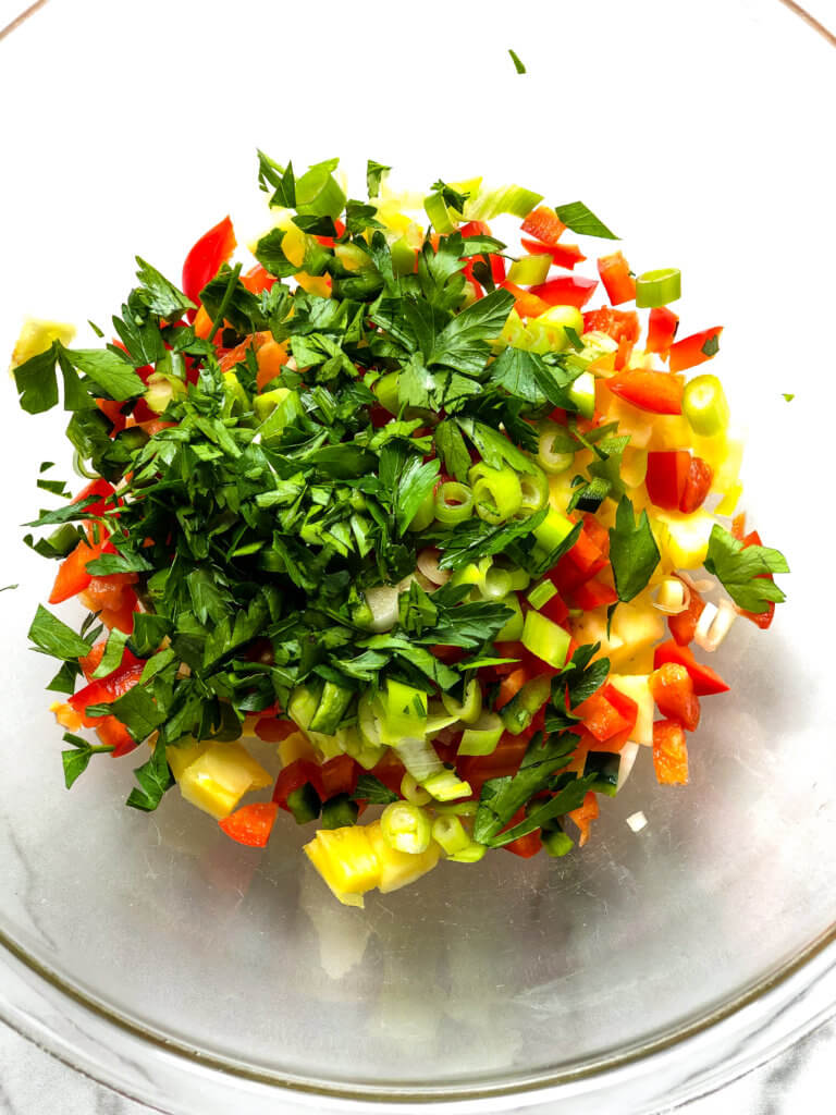 Shows Bowl of ingredients for Bacon-Pineapple salsa, chopped pineapple, sweet red pepper, spicy green pepper and parsley