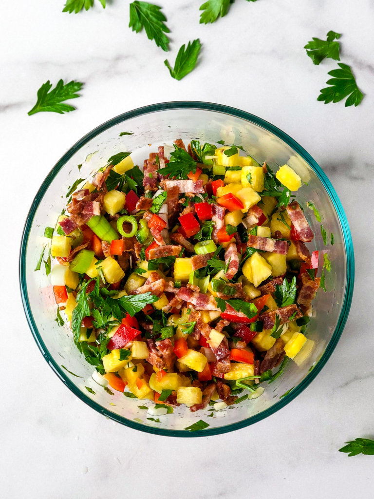 Shows bowl of Pineapple Bacon relish surrounded by parsley leaves