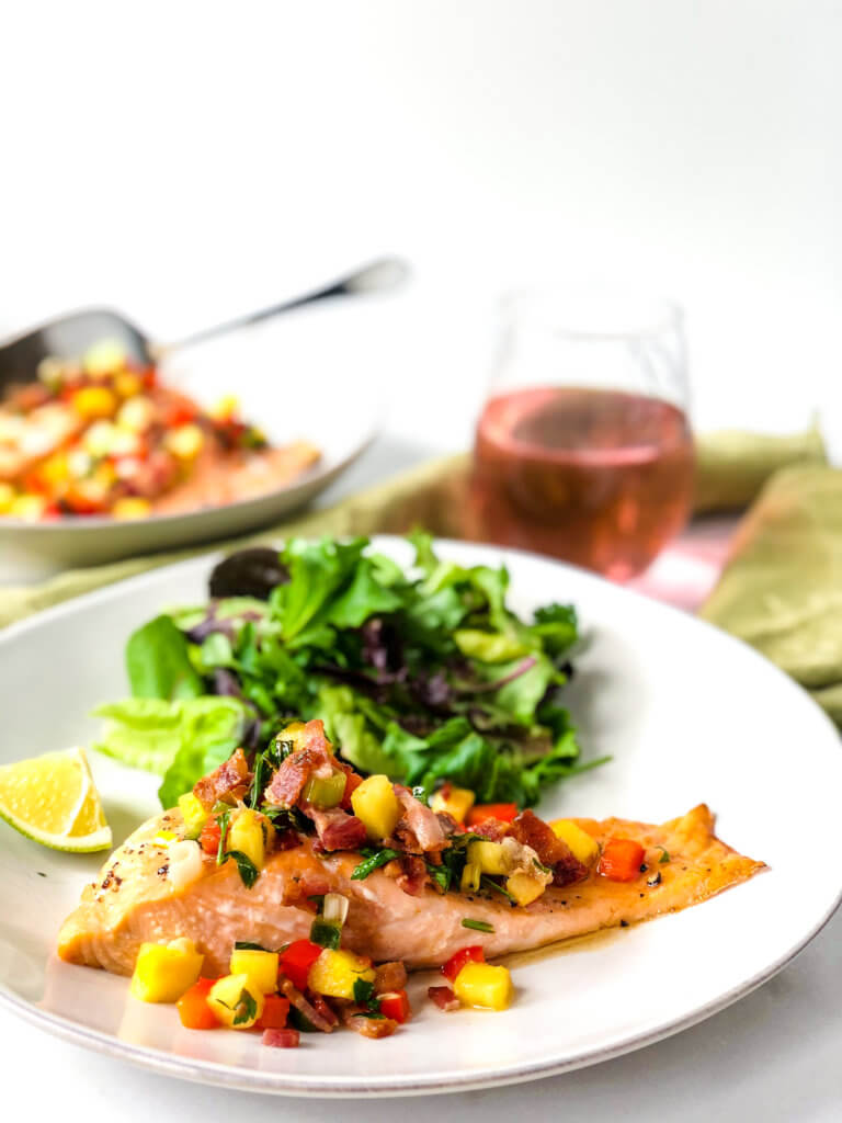 Fillet of salmon topped with pineapple bacon salsa on plate with green salad. In the background a glass of rose and bowl with more salsa-covered salmon