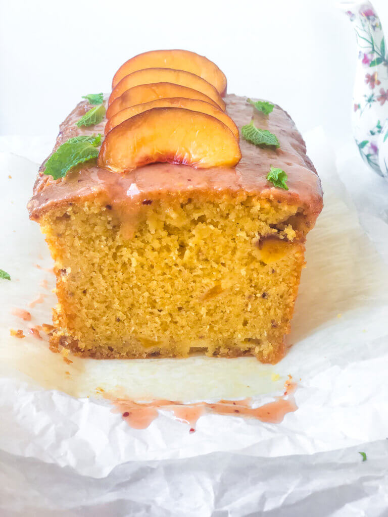 Head-on view of interior of peach lime pound cake. Shows amazing soft firm, small-crumbed texture. Slice peaches lined up with mint leaves on top of cake.