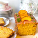 Shows peach poundcake loaf with a line of peach slices on top with a few mint leaves. Several slices on plates next to the cake. A teacup and teapot in the background