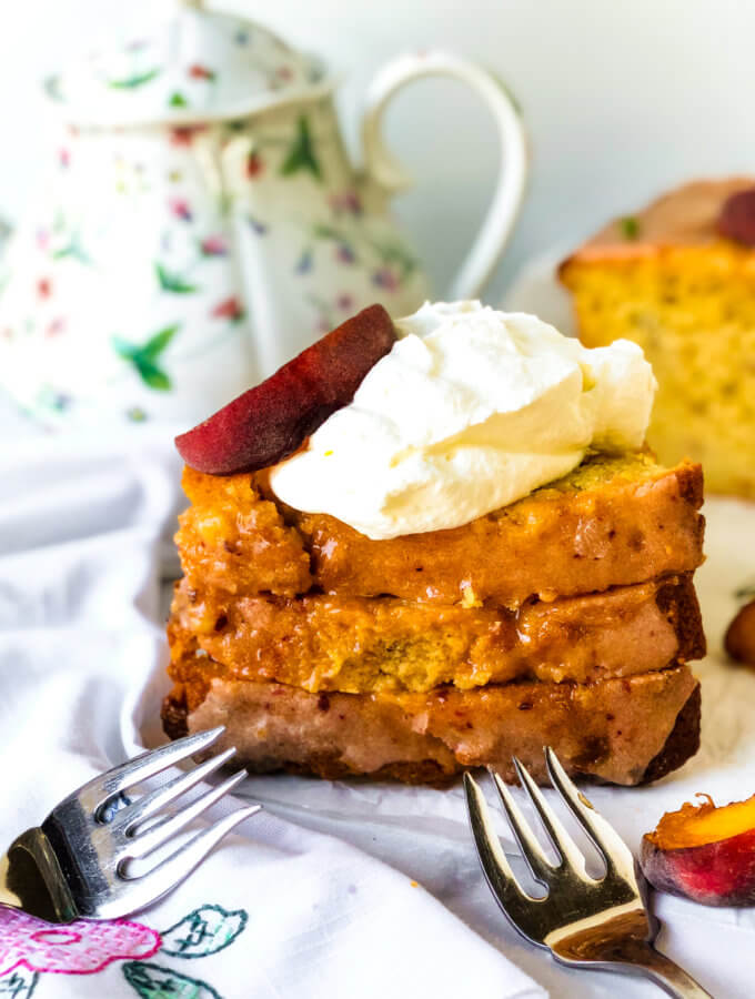 Featured image. Shows 3 stacked slices of peach lime pound cake, topped with whipped cream and peach slices. In the background is a teapot and the remainder of the loaf cake. White flowered napkin and forks strewn about white background