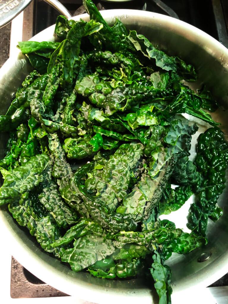 Process shot Shows kale pieces sautéing in pan