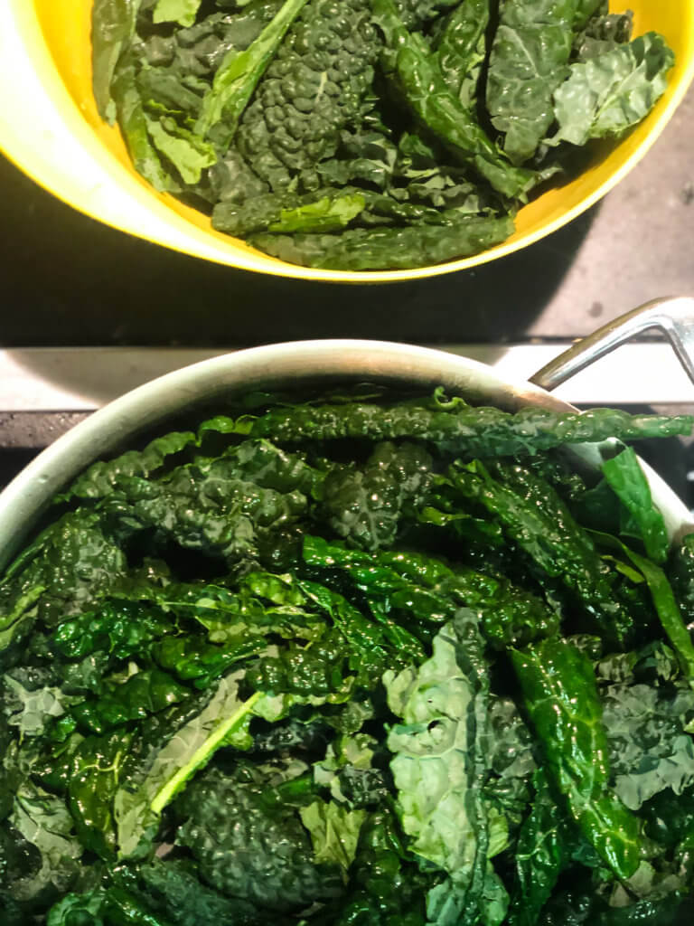 Process shot shows addition of kale to pan full of kale