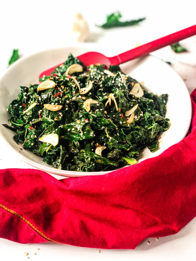 Overhead 45-degree shot of Sautéed Smoky Kale in a bowl, with red serving spoon and a red napkin in front