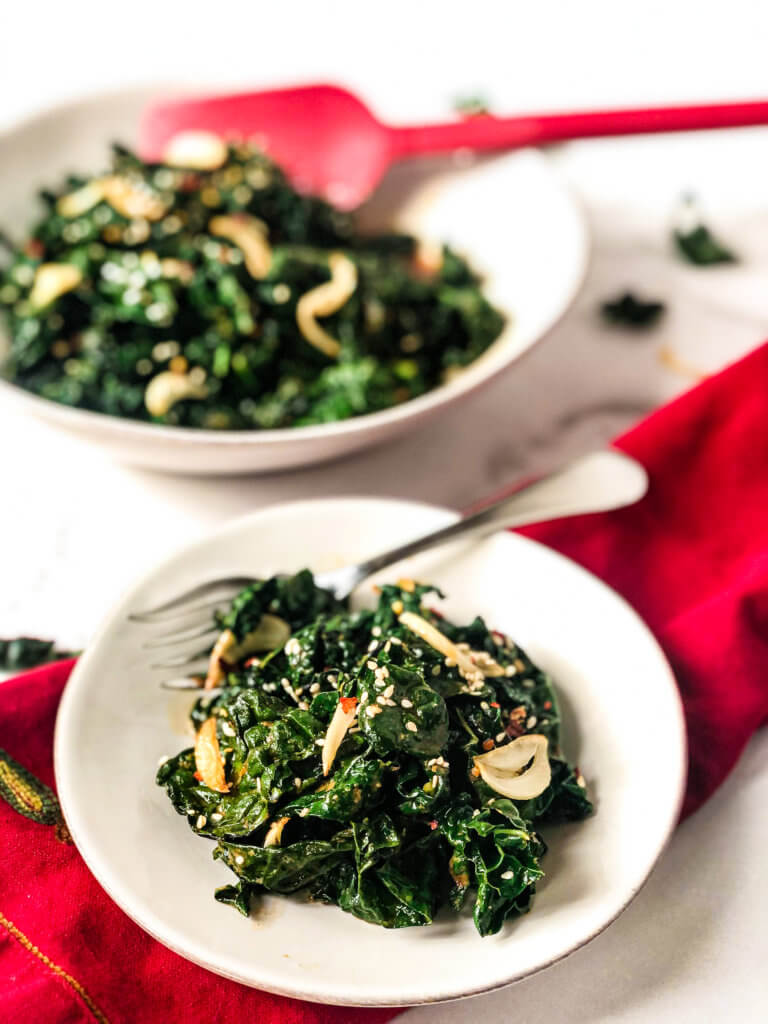 Closeup of small plate of Smoky Kale, with serving dish in the background. A red spoon in the serving dish. the small plate setting over a red napkin.