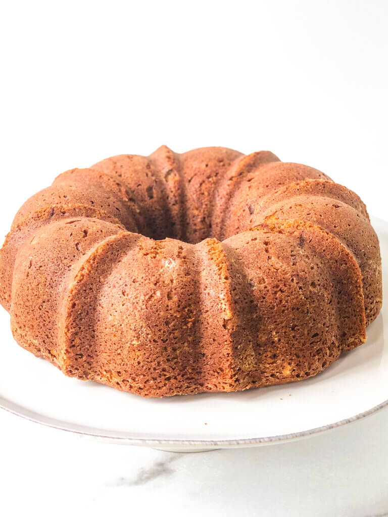 process shot Shows baked bundt cake on white cakes stand