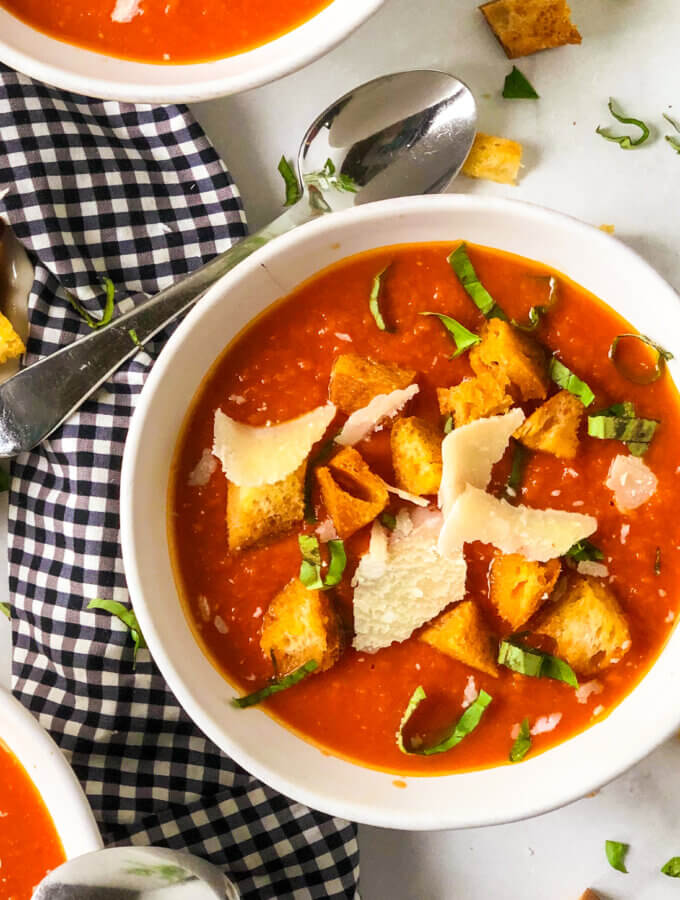 Overhead closeup of bowl of tomato white bean soup, topped with golden croutons, shreds of parmesan and bits of basil, spoon rising on black and white gingham napkin