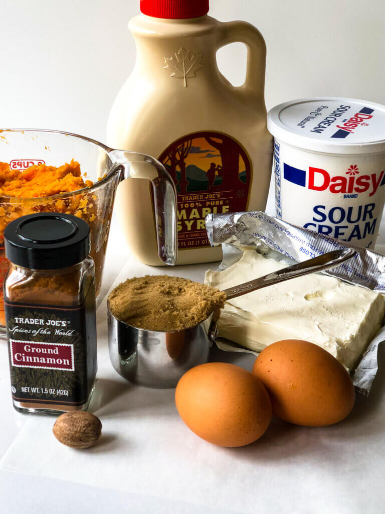 Shows ingredients for sweet potato cheesecake filling: sweet potato, maple syrup, sour cream, cream cheese, eggs, brown sugar, nutmeg, cinnamon