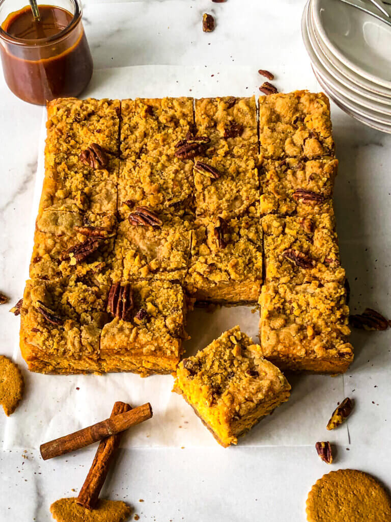 Shows Sweet Potato Cheesecake bars against white background, with scattered gingerbread cookies, cinnamon and chopped pecans