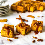 featured photo shows bar of Sweet Potato Cheesecake covered with dripping caramel. Rest of bars and jar of caramel in background