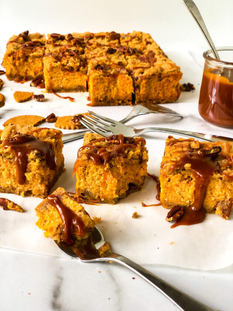 Blog photo Shows 3 slices of Sweet Potato Cheesecake in foreground, a bite taken out of one with a fork, remaining bars and jar of caramel in background