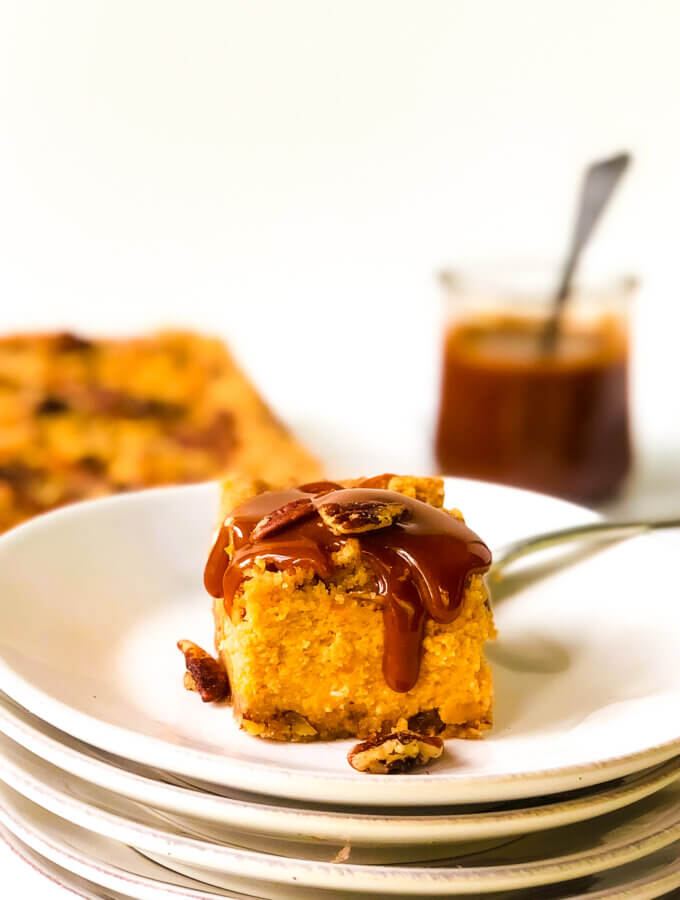 First photo in post shows bar of Sweet Potato Cheesecake covered with dripping caramel. Rest of bars and jar of caramel in background
