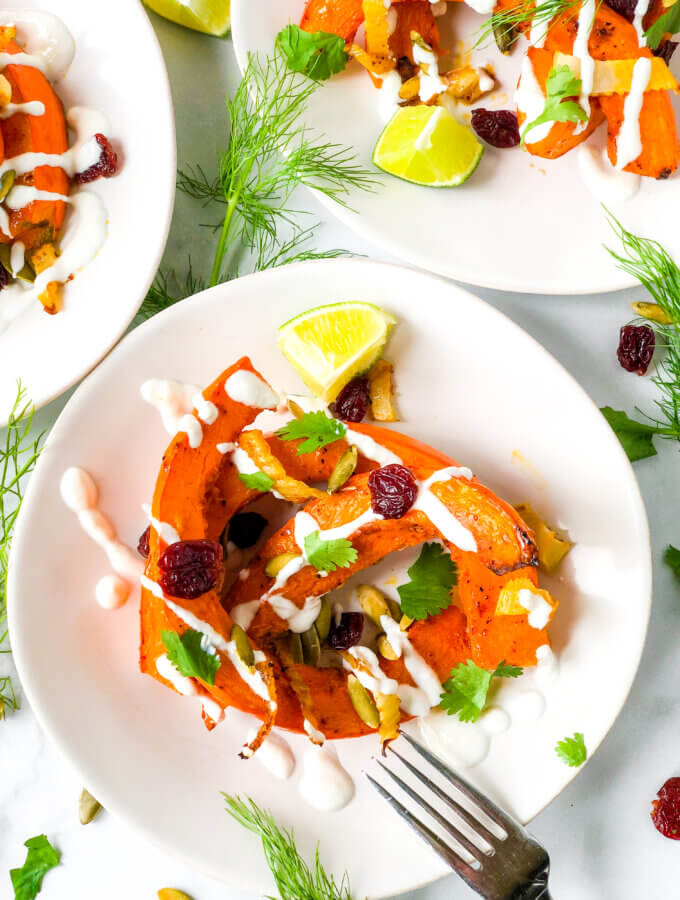 Overhead shot Shows dressed salads of red kuri squash crescents, dried cherries, and pepitas, all topped with creamy dressing