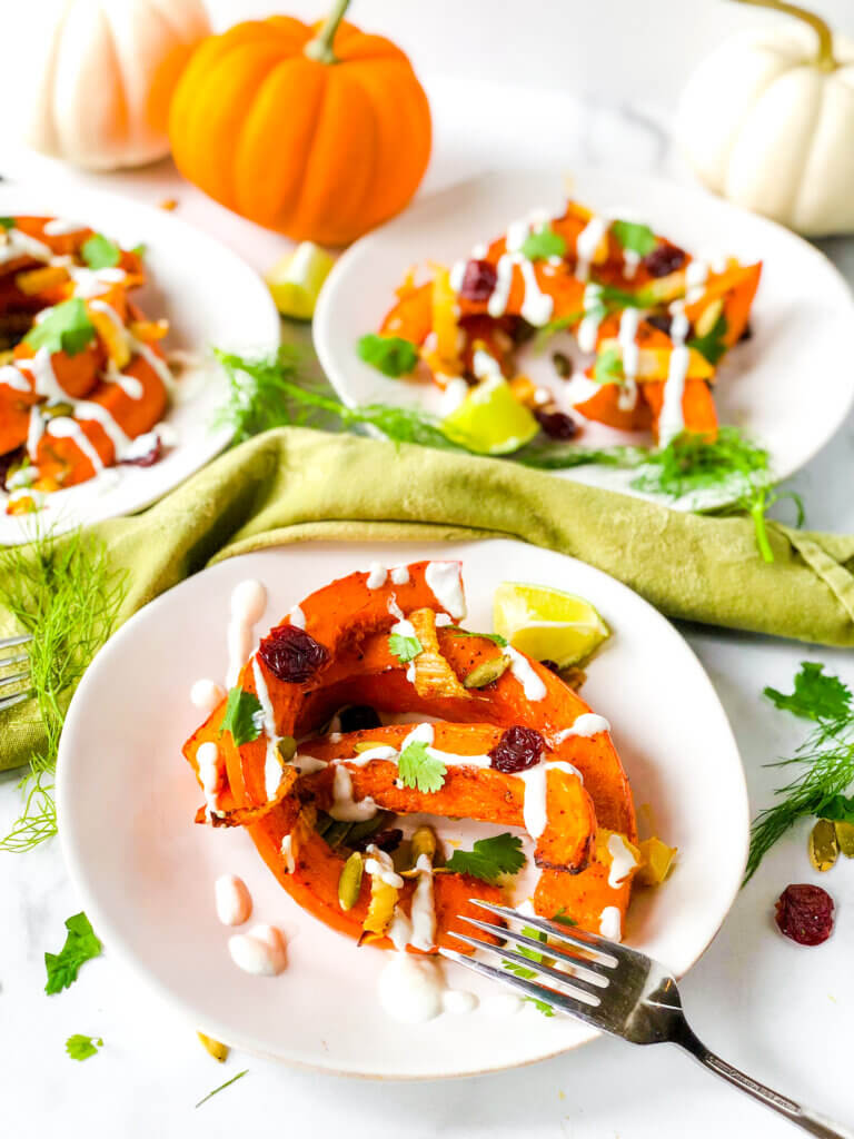 Blog photo Showing dressed salads of red kuri squash crescents, dried cherries, and pepitas, all topped with creamy dressing