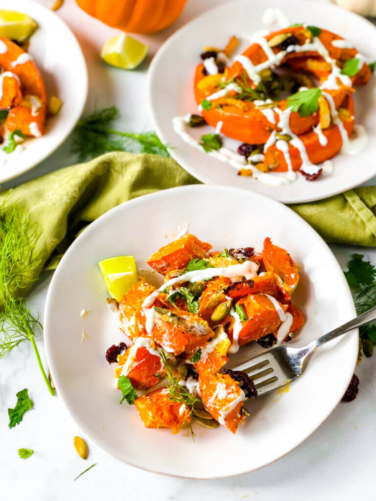 Shows dressed salads of red kuri squash crescents, dried cherries, and pepitas, all topped with creamy dressing
