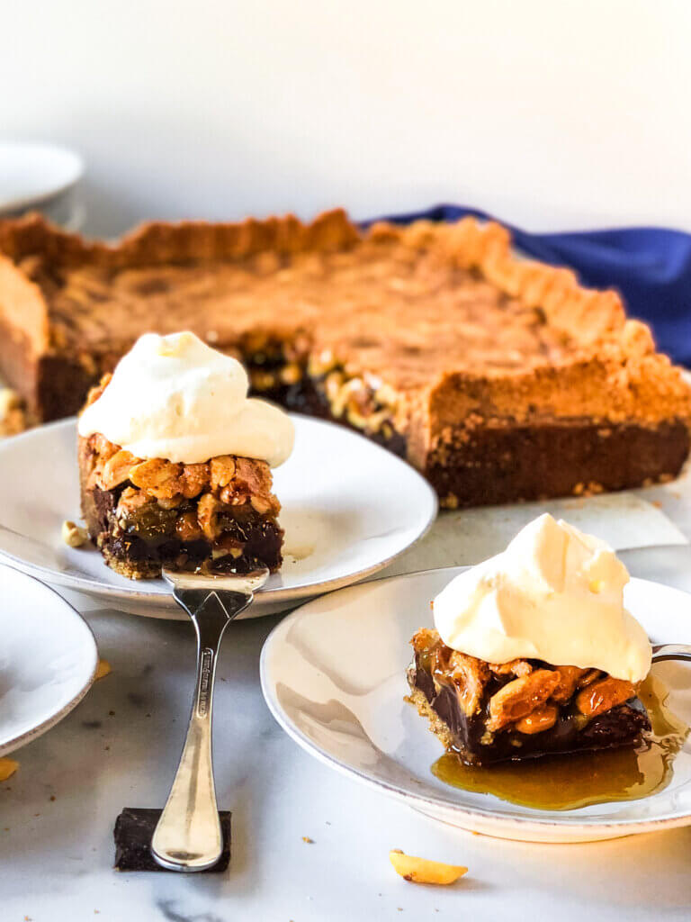 Blog photo showing chocolate peanut pie bars with whipped cream