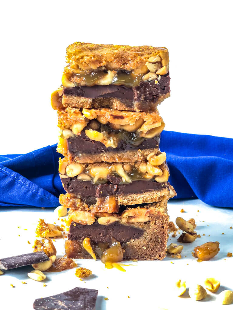 Stack of 4 Black-Bottom Peanut Pie bars with layer of ganache, peanuts and cookie crust.