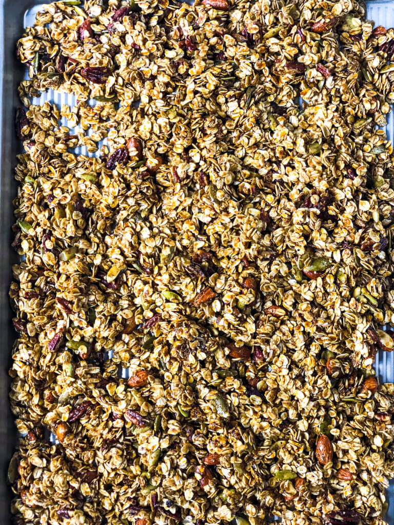 Part of process of making Gingerbread granola: Overhead shot of unbaked Gingerbread Granola mix spread to edges of sheet pan to bake