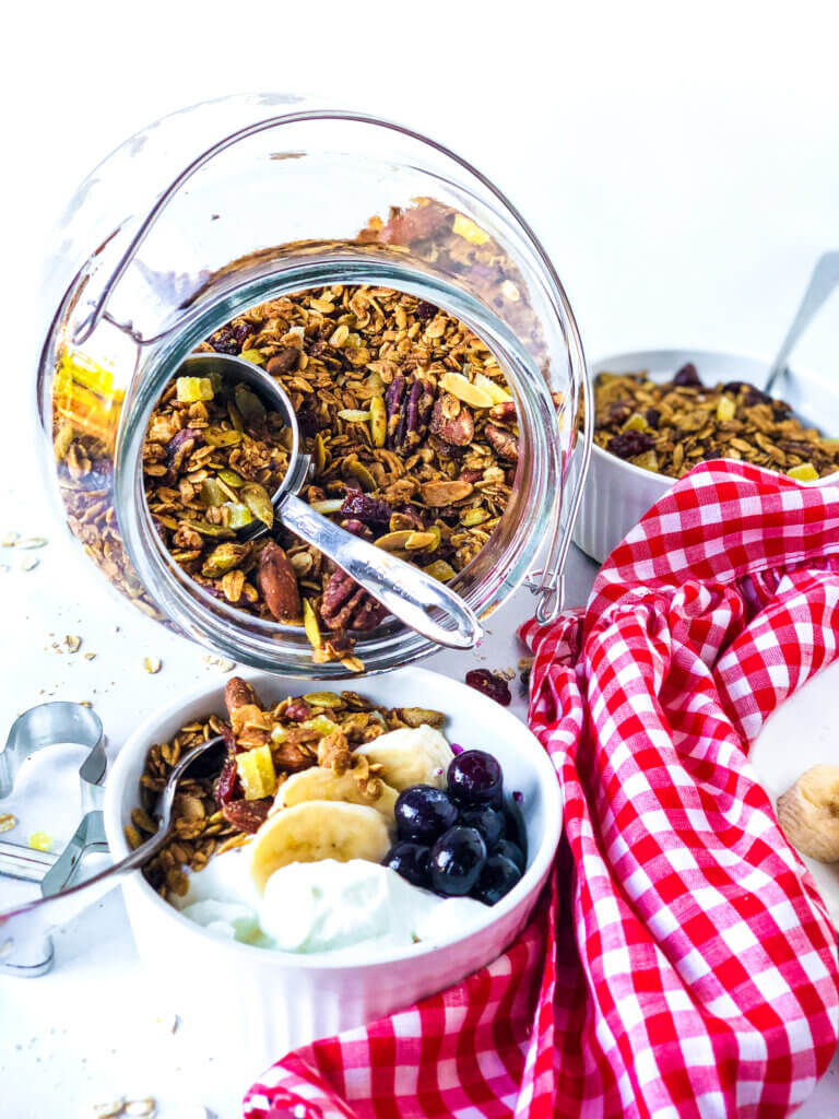 Blog image showing jar of gingerbread granola tipped over into a white bowl with granola, yogurt, blueberries and banana slices. Red gingham napkin at right side and gingerbread man cookie cutter at left