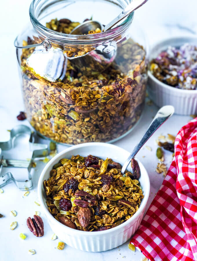 Blog photo showing jar of granola, and ramekin in front and at the side, each containing granola. Toward front is red gingham napkin