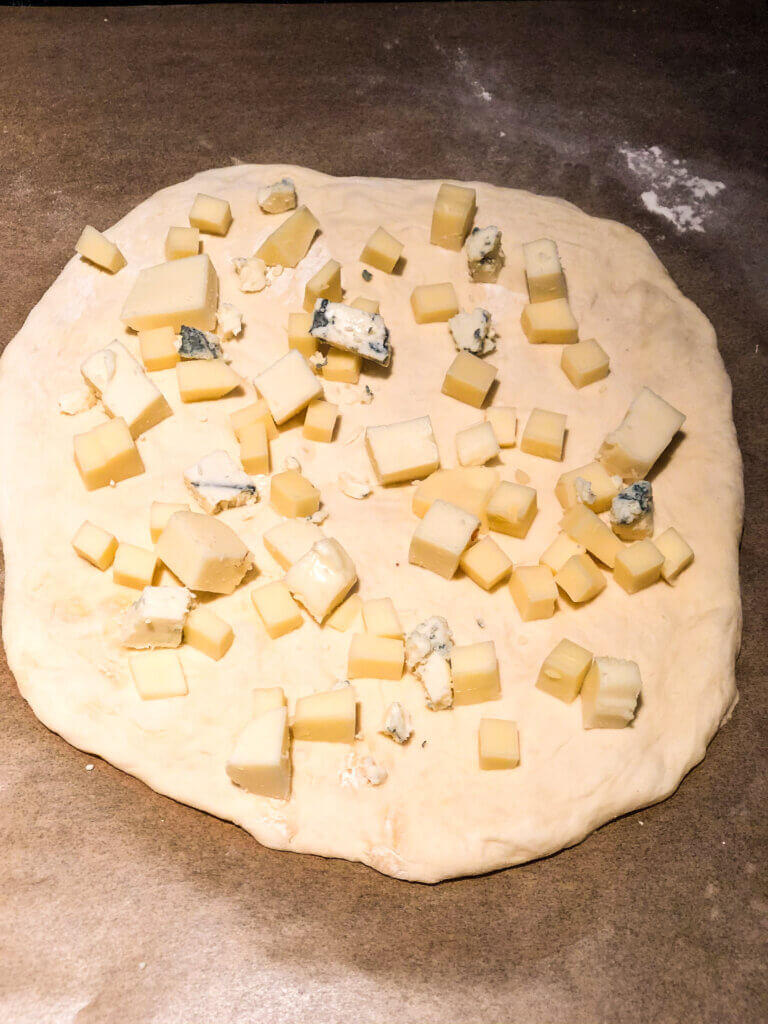 Process shot for making honey badger pizza, showing overhead view of raw crust spinkled with chunks of mozzarella, provolone and bits of gorgonzola cheese