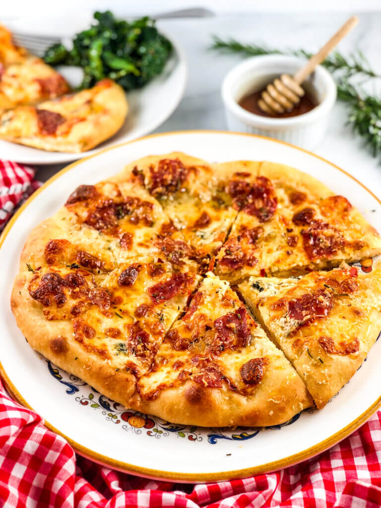 Shows fully baked, golden brown-crusted, melty cheese, salami all over pizza. Behind the pizza are a pot of honey for drizzling and a plate with pizza and a green salad. Red/white gingham napkin in the foreground