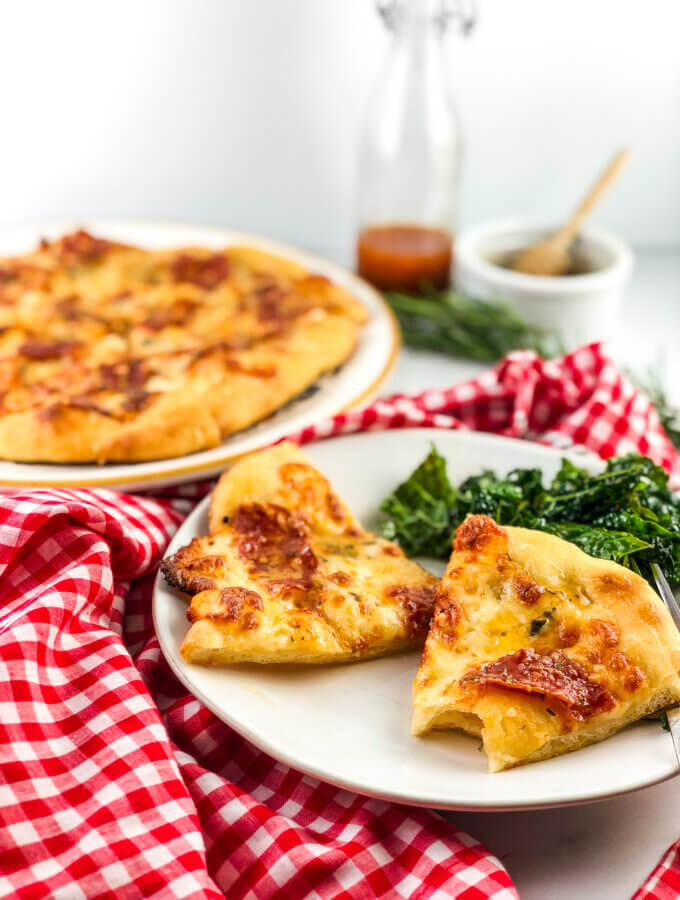 Blog post photo 45-degree view of slices of pizza, drizzled with shimmering honey, with whole pizza in background along with a honey pot and salad dressing cruet