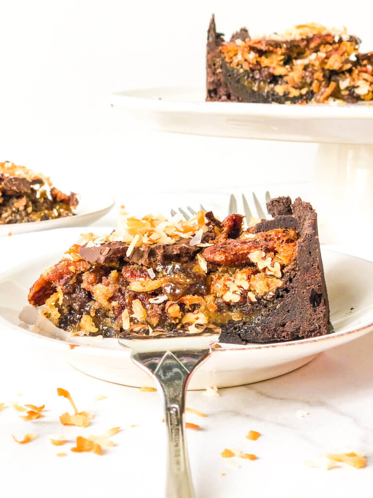 Blog post photo showing Close-up, head-on view of slice of chocolate pecan pie tart with dollop of whipped cream. In background is cake stand with remaining pie. All on white background with fork, scattered toasted coconut and pecans.