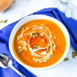 Shows single bowl of sweet potato soup topped with swirl of cream, pepitas and sprinkle of smoked paprika