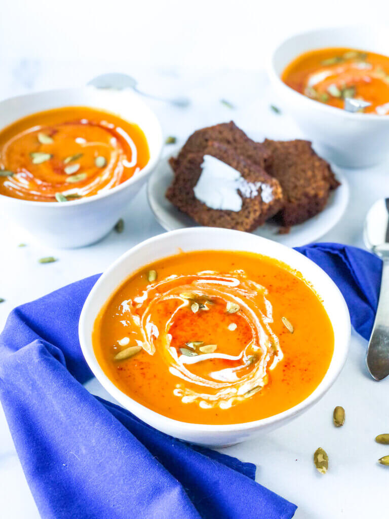 overhead shot of 3 bowls smoky sweet potato soup, each topped with swirl of sour cream, paprika and roasted pepitas