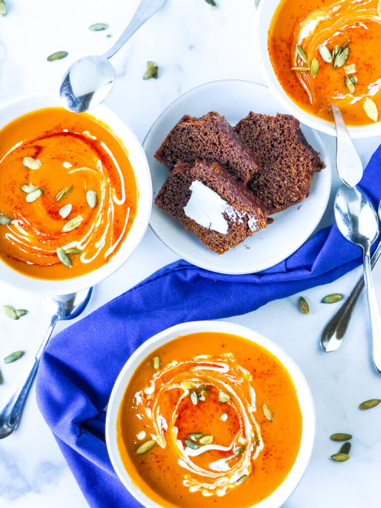 overhead view of 3 scattered bowls of smoky sweet potato butternut soup with a plate of buttered brown bread in the middle. scattered spoons and pepitas with a blue napkin. All on marble slab