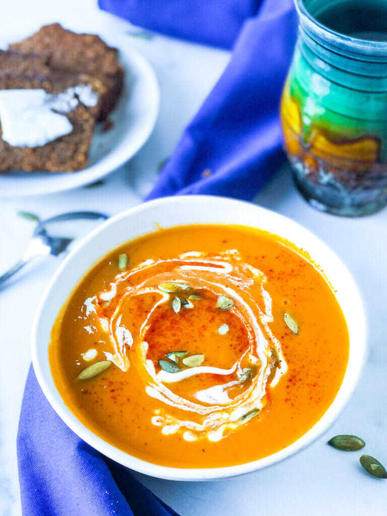 Bowl of sweet potato soup with green mug and plate of buttered brown bread in background.