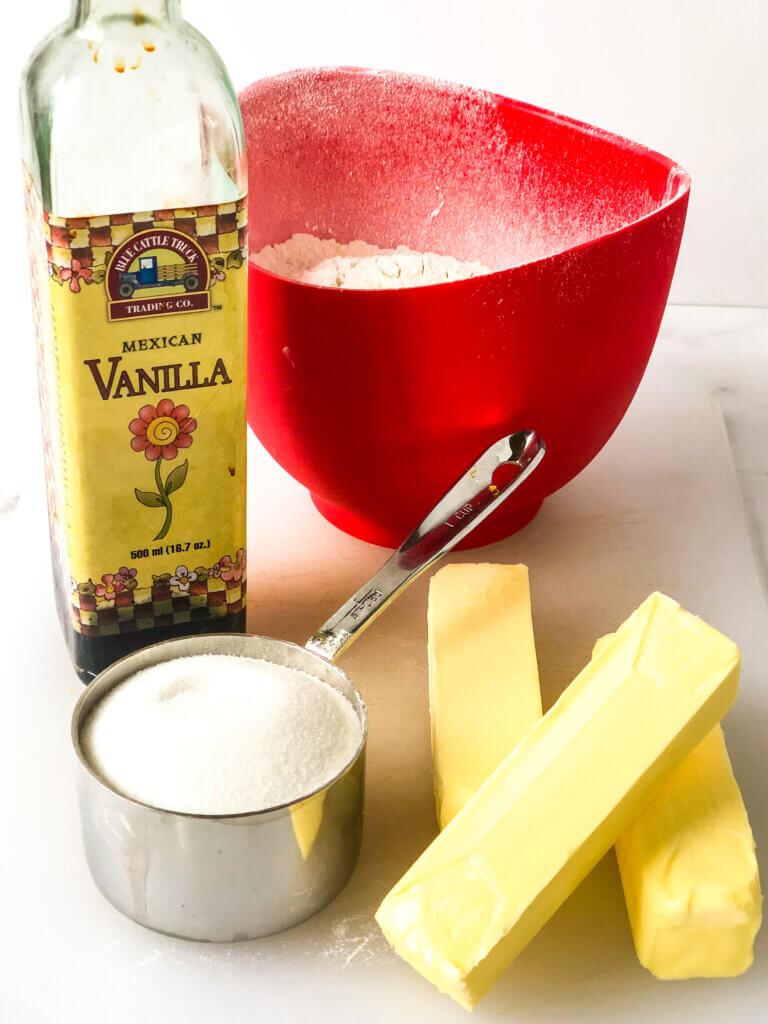 Process shot showing dough ingredients: sugar, butter, flour, vanilla, salt