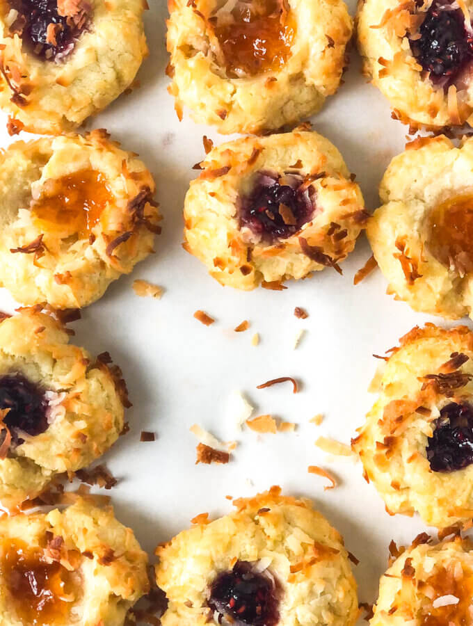 Blog photo showing closeup of grid of apricot and raspberry thumbprint cookies, and scattered toasted coconut