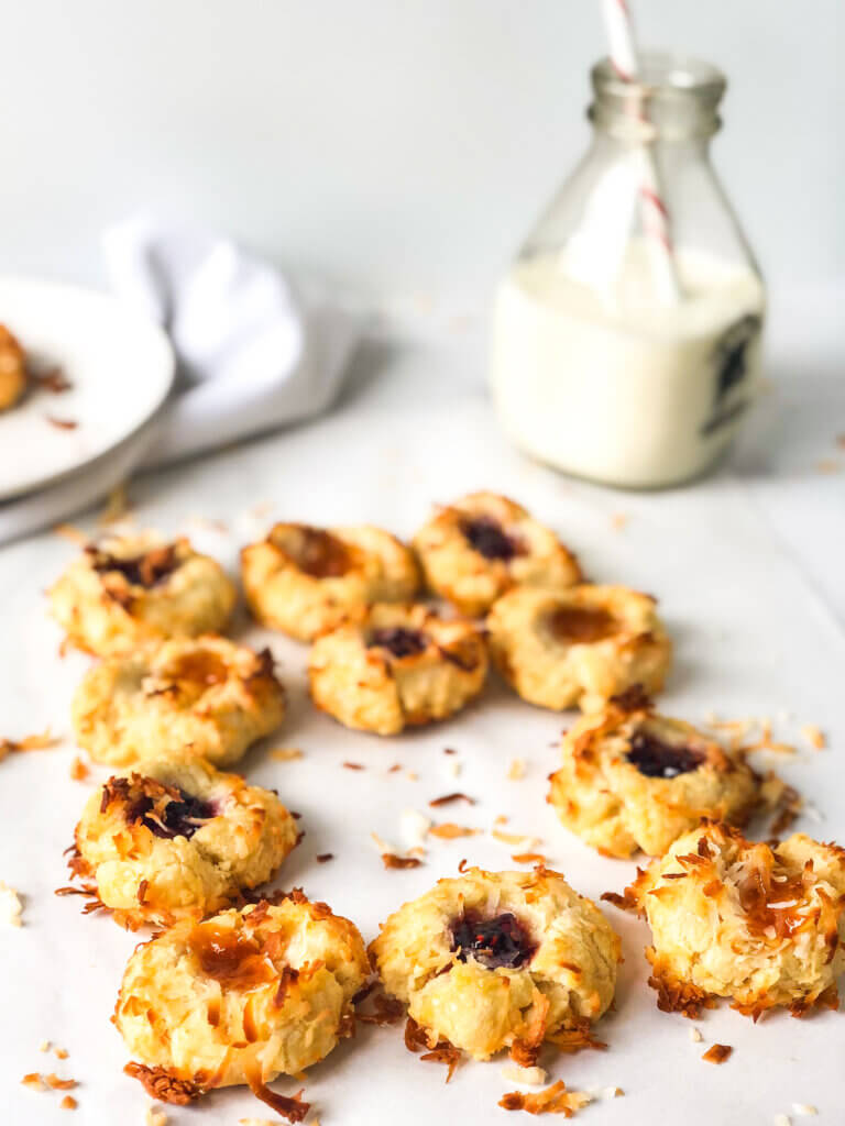 Blog post photo showing an array of apricot and raspberry coconut-coated thumbprint cookies, with one missing. Bottle of milk with straw, plates and cookie on white napkin in the white background
